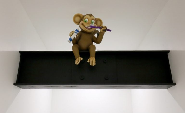 A baby monkey brushing his teeth on a ceiling beam.