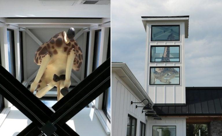 A look underneath a massive, galloping giraffe sculpture.
